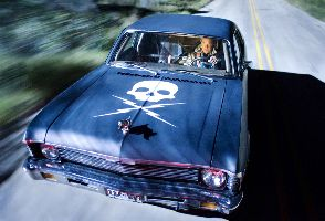 Kurt Russell can't understand why the car roof hasn't cast a shadow on his face...