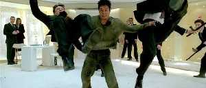 Jet Li tries to fly out of trouble by flapping two goons, with limited success.